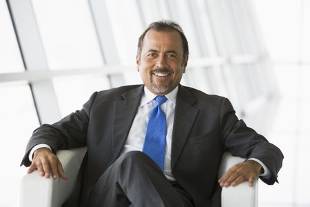 Businessman sitting indoors smiling (high key/selective focus) Stock Photo - 3171737
