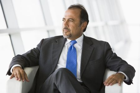 Businessman sitting indoors looking out window (high key/selective focus) Stock Photo - 3171744