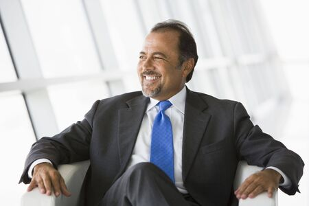 windowpanes: Businessman sitting indoors looking out window smiling (high keyselective focus)