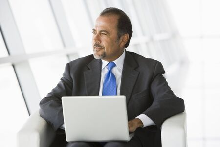 Businessman sitting indoors with laptop looking out window (high key/selective focus) Stock Photo - 3171725