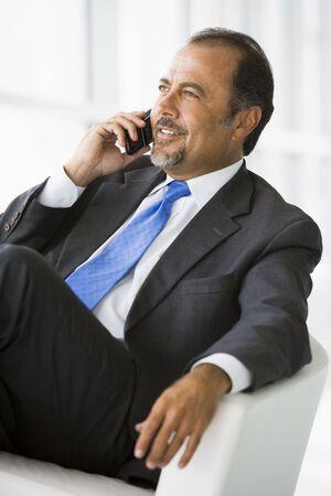 Businessman sitting indoors on cellular phone smiling (high keyselective focus) photo