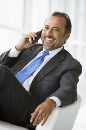 Businessman sitting indoors on cellular phone smiling (high keyselective focus) photo