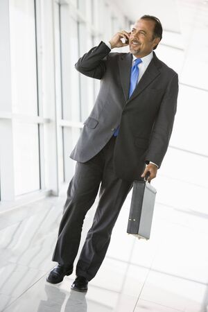 Businessman walking in corridor on cellular phone smiling (high keyselective focus) photo