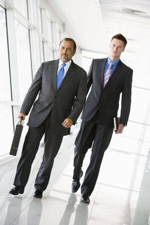Two businessmen walking in a corridor (high keyselective focus) photo