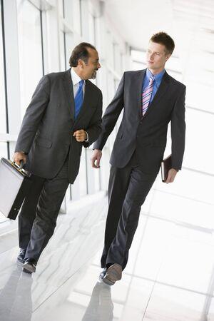 Two businessmen walking in a corridor talking (high keyselective focus)