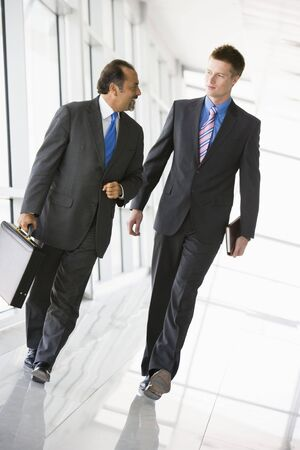 mature business man: Two businessmen walking in a corridor talking (high keyselective focus)