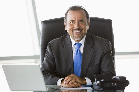 communicatie: Zakenman in kantoor met laptop lachend (high key  selectieve focus)