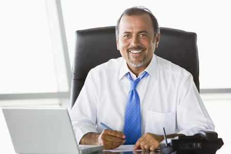 Businessman in office with laptop smiling (high key/selective focus)