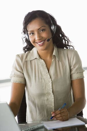 handsfree telephones: Businesswoman wearing headset in office by laptop smiling (high keyselective focus) Stock Photo