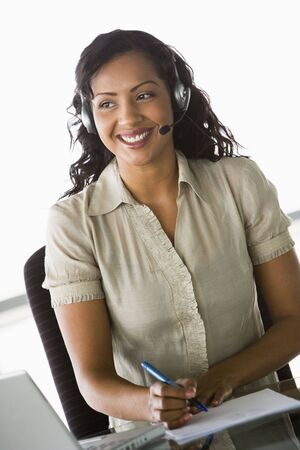 Businesswoman wearing headset in office by laptop smiling (high key/selective focus) Stock Photo - 3170977