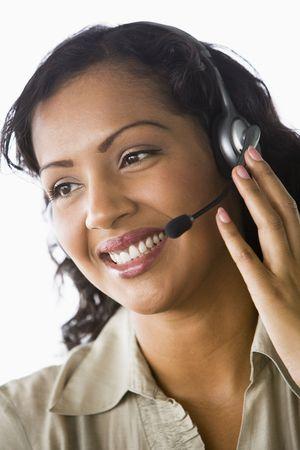mobile headset: Empresaria usar auriculares en la oficina sonriendo (clave de alta  selectiva enfoque)  Foto de archivo