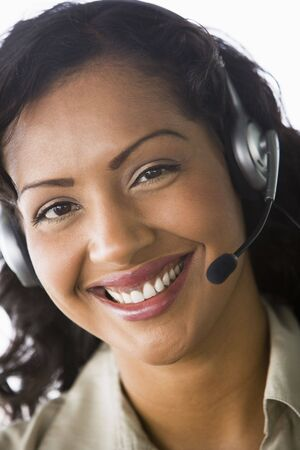 handsfree telephones: Businesswoman wearing headset in office smiling (high keyselective focus) Stock Photo