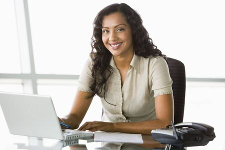 Businesswoman in office with laptop smiling (high key/selective focus) Stock Photo - 3171098