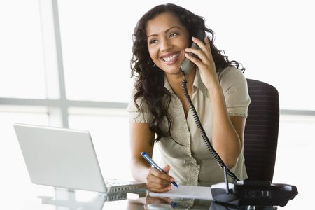 com: Businesswoman in office on telephone by laptop smiling (high keyselective focus)