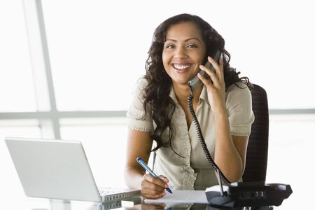 windowpanes: Businesswoman in office on telephone by laptop smiling (high keyselective focus)