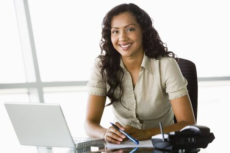 Businesswoman in office with laptop smiling (high key/selective focus)