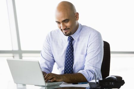 Businessman in office with laptop smiling (high key/selective focus) Stock Photo - 3171230