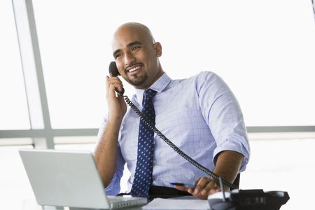 Businessman in office on telephone by laptop smiling (high keyselective focus) photo