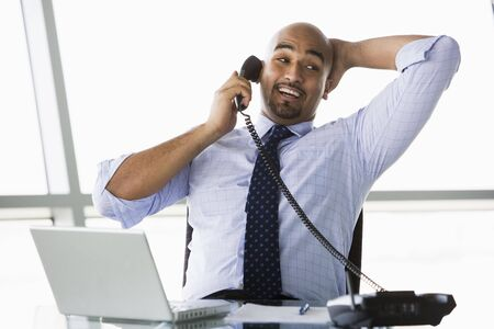 Businessman in office on telephone by laptop smiling (high key/selective focus) Stock Photo - 3171081