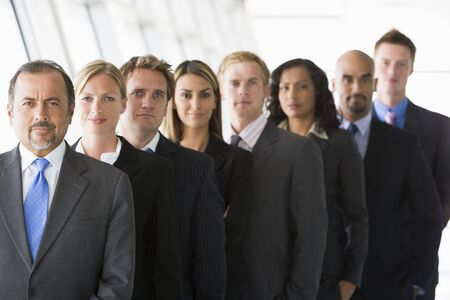 medium group: Group of co-workers standing in office space smiling (high keydepth of field)