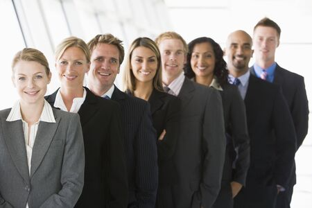 corporation: Group of co-workers standing in office space smiling (high keydepth of field)