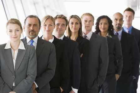 windowpanes: Group of co-workers standing in office space smiling (high keydepth of field)