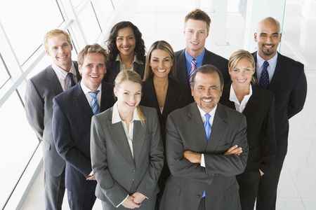 company employee: Group of co-workers standing in office space smiling (high key) Stock Photo