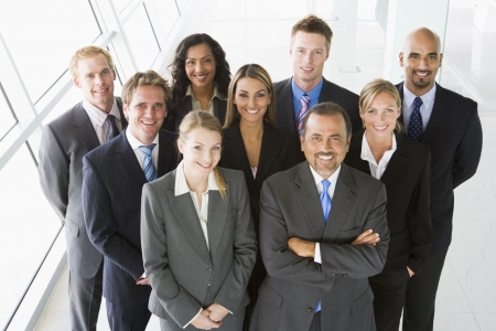 corporation: Group of co-workers standing in office space smiling (high key) Stock Photo