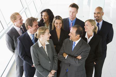 high key: Gruppo di collaboratori in piedi in uno spazio ufficio sorridente (alta chiave)