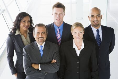 windowpanes: Group of co-workers standing in office space smiling (high key) Stock Photo