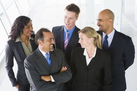 Group of co-workers standing in office space smiling (high key) Stock Photo - 3171013