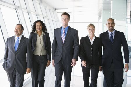 windowpanes: Group of co-workers walking in office space smiling (high key) Stock Photo