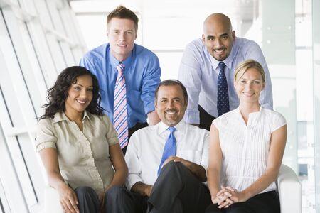east meets west: Five businesspeople indoors smiling (high keyselective focus)