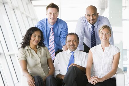 Five businesspeople indoors smiling (high keyselective focus) photo