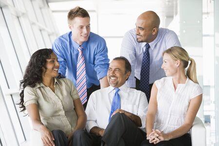 Five businesspeople indoors smiling (high keyselective focus)