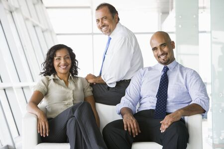 Three businesspeople sitting indoors smiling (high key/selective focus) Stock Photo - 3174531