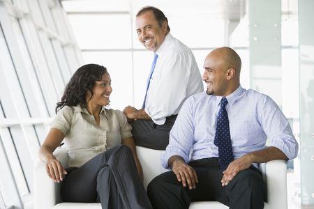 windowpanes: Three businesspeople sitting indoors smiling (high keyselective focus) Stock Photo