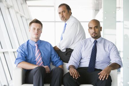 Three businessmen sitting indoors (high key/selective focus) photo