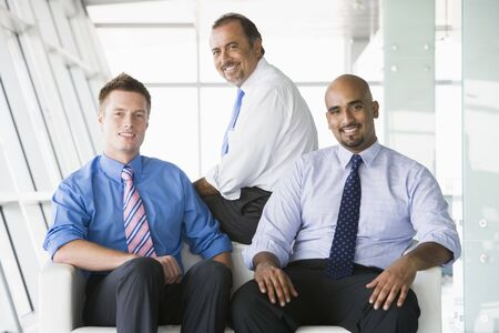 caucasoid race: Three businessmen sitting indoors smiling (high keyselective focus)