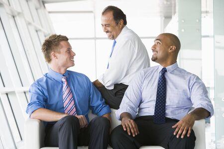 Three businessmen sitting indoors smiling (high keyselective focus)