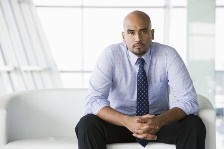 Businessman sitting indoors (high key/selective focus) photo