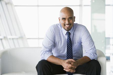 Businessman sitting indoors smiling (high key/selective focus) Stock Photo - 3171243