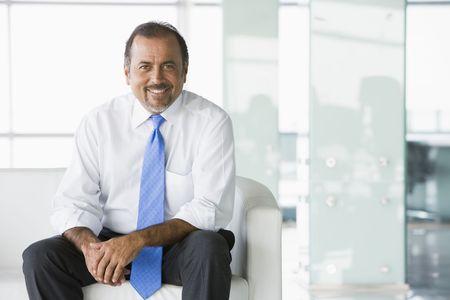 Businessman sitting indoors smiling (high key/selective focus) photo