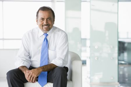 windowpanes: Businessman sitting indoors smiling (high keyselective focus) Stock Photo