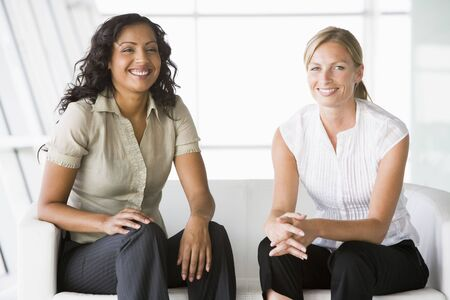 Two businesswomen sitting indoors smiling (high keyselective focus)