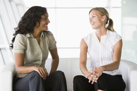 Two businesswomen sitting indoors talking and smiling (high key/selective focus) Stock Photo - 3170988