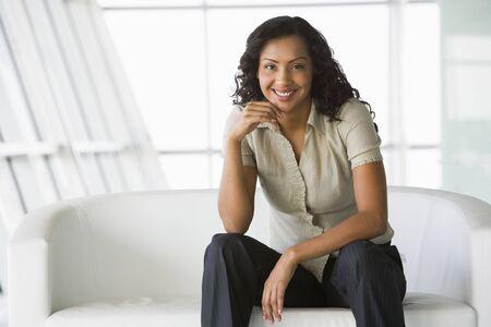 windowpanes: Businesswoman sitting indoors smiling (high keyselective focus) Stock Photo