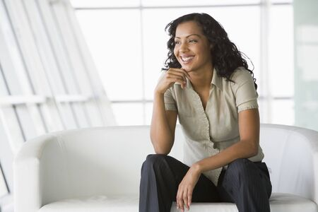 windowpanes: Businesswoman sitting indoors smiling (high keyselective focus) Stock Photo