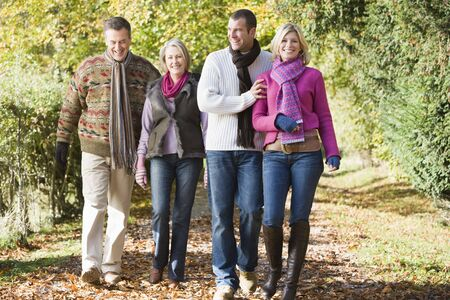 Two couples walking outdoors in park smiling photo