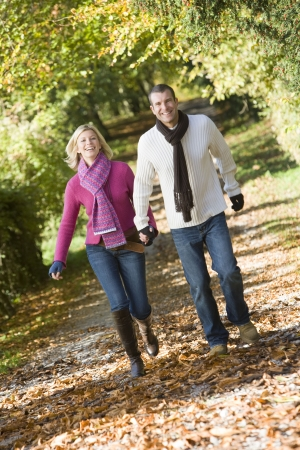 Couple outdoors running on path in park holding hands smiling (selective focus) photo
